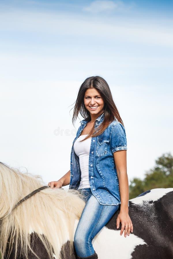 Chica joven hermosa que se sienta en caballo fotografía de archivo libre de regalías
