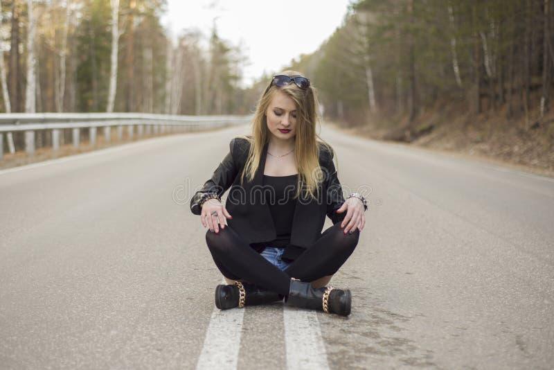 Chica joven hermosa que se sienta en el medio del camino fotografía de archivo
