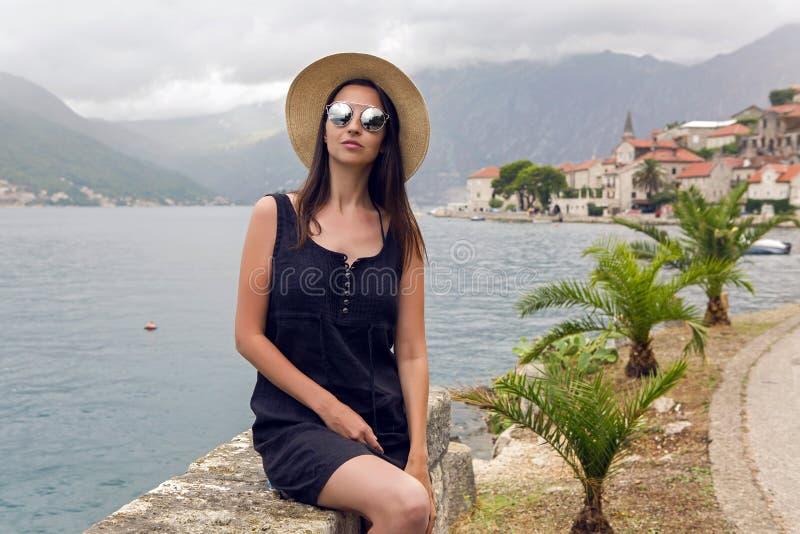 Chica joven hermosa que se sienta en sombrero en el fondo de montañas y del mar imagen de archivo libre de regalías