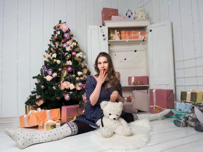 Chica joven hermosa que se sienta en una astilla entre regalos y un árbol de navidad fotografía de archivo