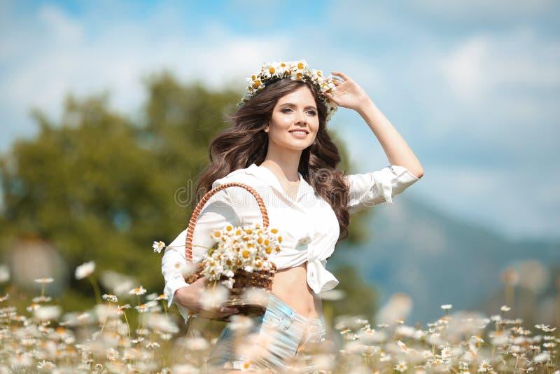 Chica joven hermosa que sonríe con la cesta de flores sobre campo de la manzanilla Mujer morena feliz despreocupada con el pelo o imagen de archivo libre de regalías