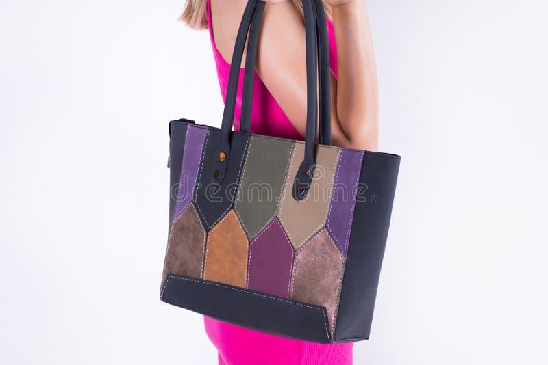 Chica joven hermosa que sostiene el bolso en la parte posterior y la muchacha en vestido rosado imágenes de archivo libres de regalías