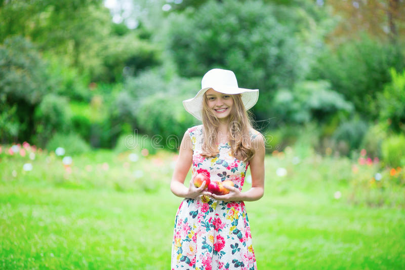 Chica joven hermosa que sostiene manzanas imagen de archivo