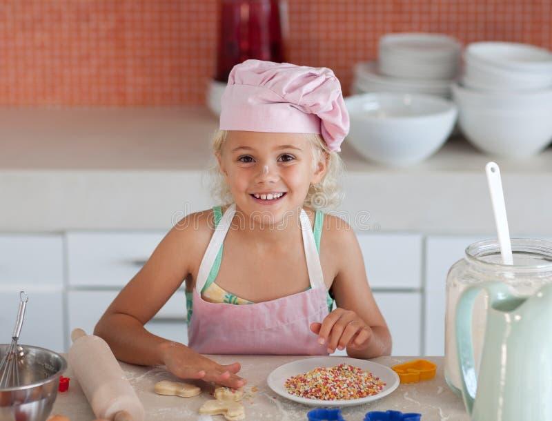 Chica joven hermosa que trabaja en la cocina foto de archivo