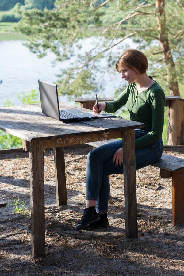 Chica joven hermosa que usa su tableta gráfica al aire libre fotografía de archivo libre de regalías