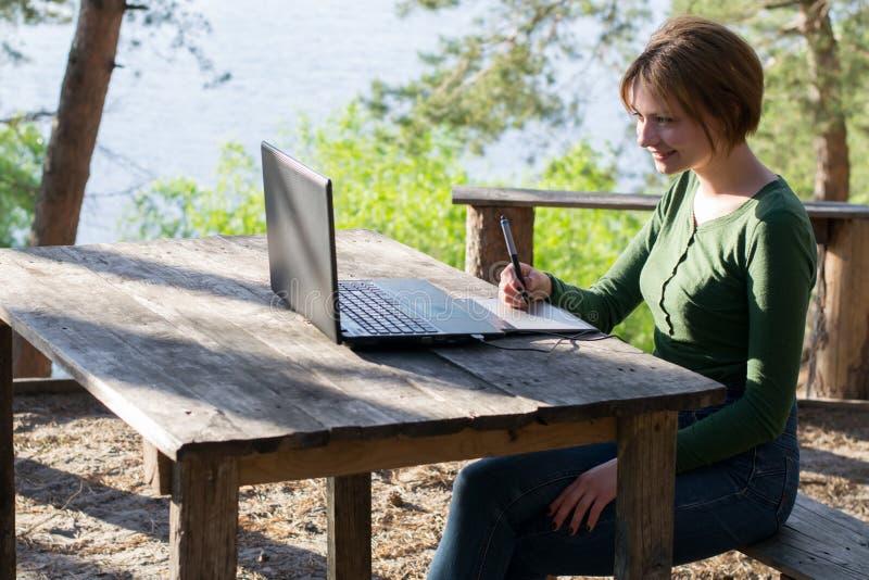 Chica joven hermosa que usa su tableta gráfica al aire libre imagen de archivo