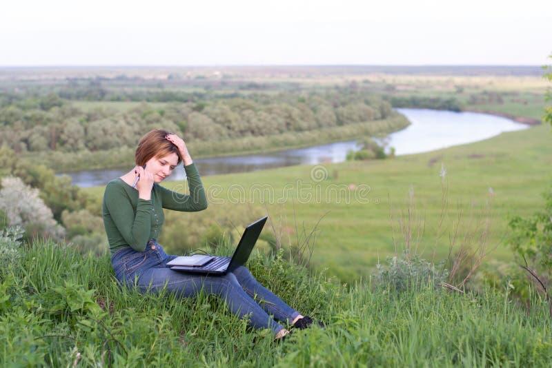 Chica joven hermosa que usa su tableta gráfica que se sienta en la hierba cerca del río fotos de archivo