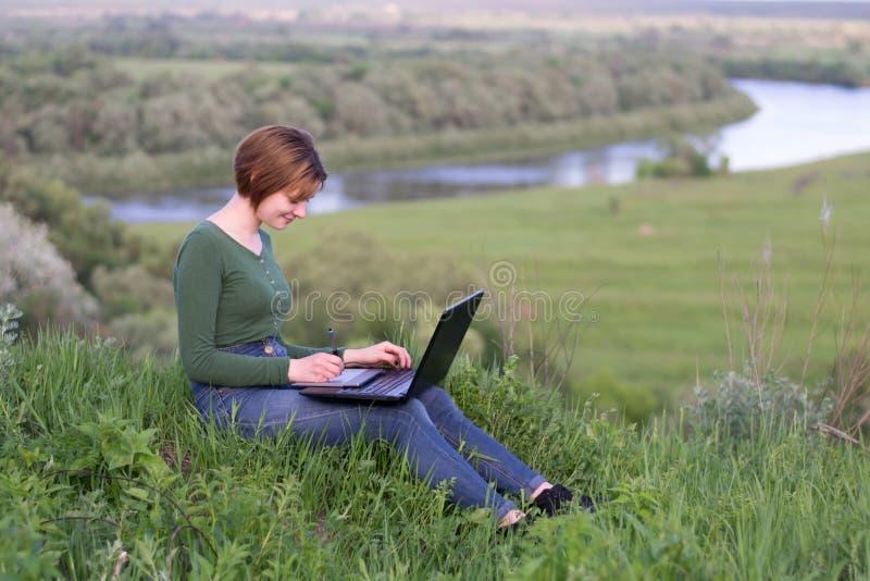 Chica joven hermosa que usa su tableta gráfica que se sienta en la hierba cerca del río imagenes de archivo