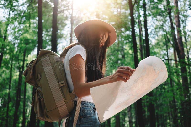 Chica joven hermosa que viaja entre árboles en bosque en la puesta del sol fotografía de archivo