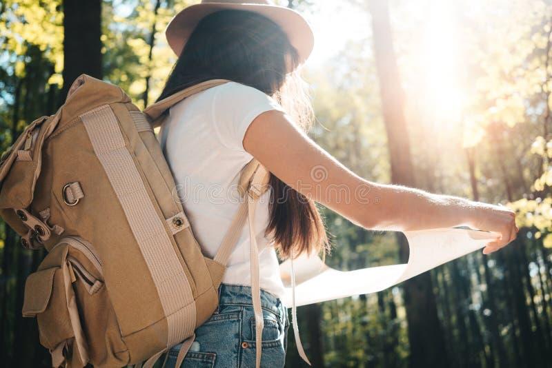 Chica joven hermosa que viaja entre árboles en bosque en la puesta del sol La mochila y el sombrero que llevan de la mujer se sos fotos de archivo