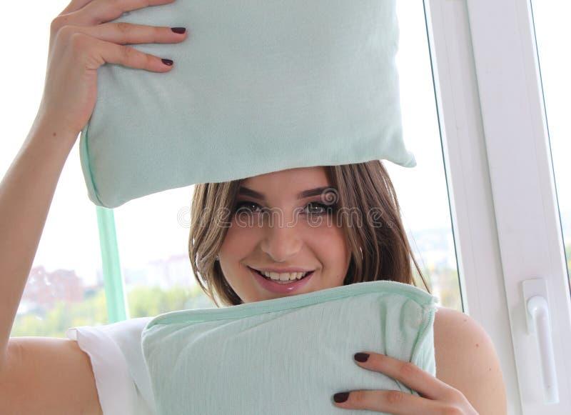 Chica joven hermosa sosteniendo las almohadas estudio foto de archivo
