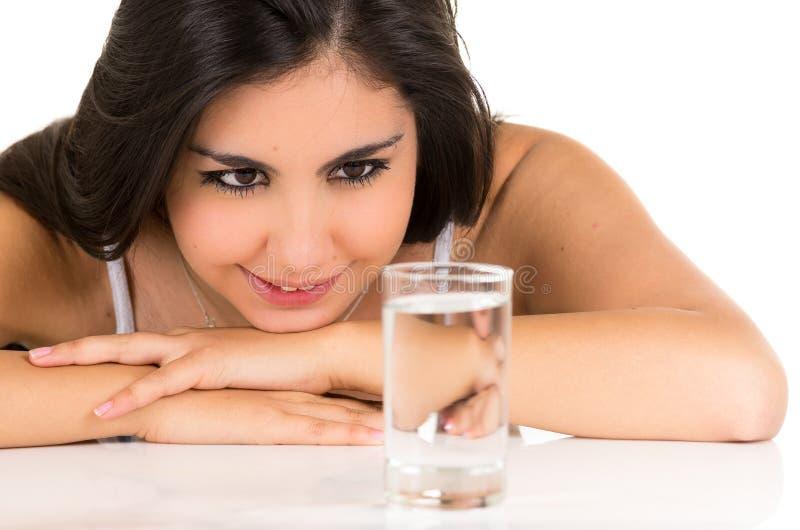 Chica joven hispánica magnífica que sonríe con un vidrio fotografía de archivo libre de regalías