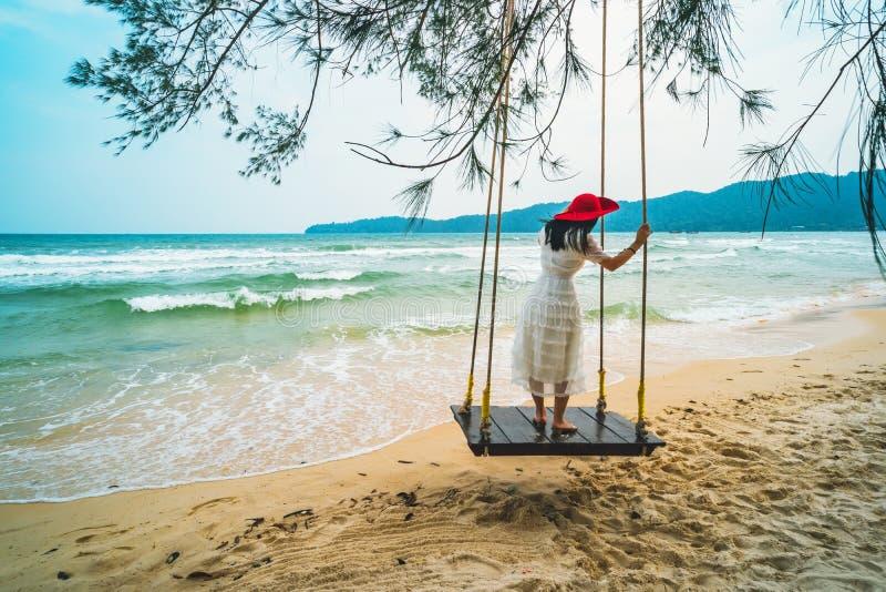 Chica joven imponente del retrato de la moda de la forma de vida del aire libre que goza en el oscilaci?n en la isla tropical En  imagenes de archivo