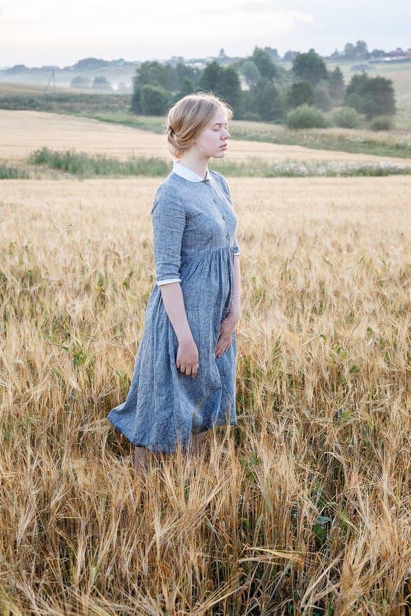 Chica joven linda agradable en vestido al aire libre pasado de moda azul en el campo de oro de oídos en la salida del sol Arboled fotos de archivo