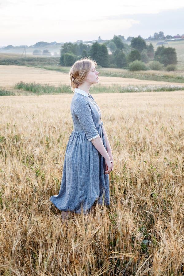 Chica joven linda agradable en vestido al aire libre pasado de moda azul en el campo de oro de oídos en la salida del sol Arboled fotografía de archivo libre de regalías