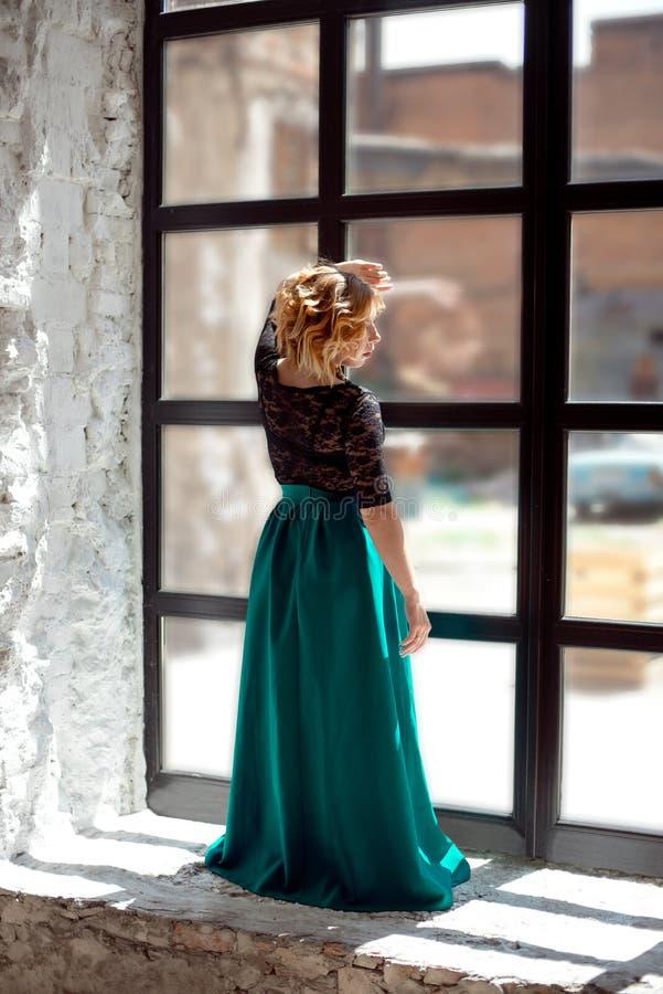 Chica joven linda con los ojos cerrados que se colocan cerca de la ventana en casa y que disfrutan de la luz caliente del sol foto de archivo