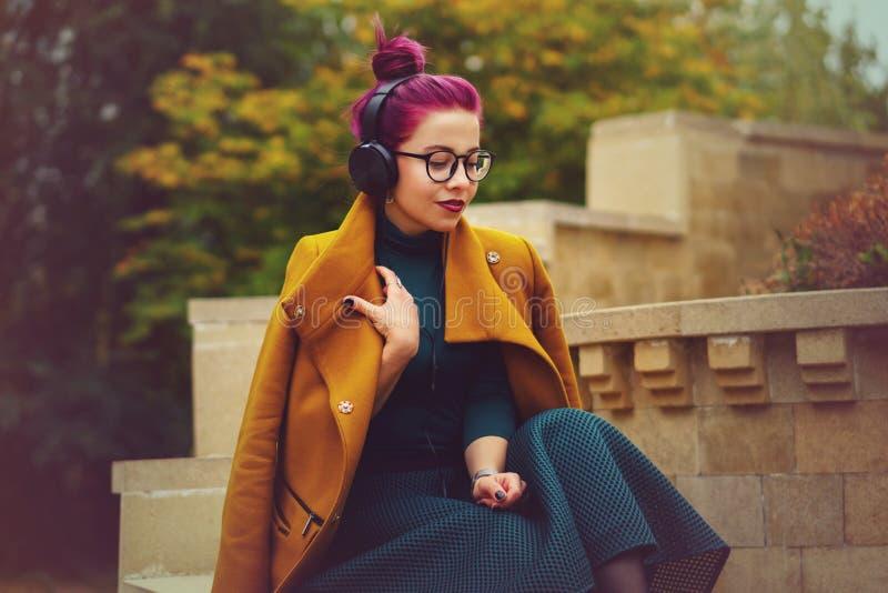 Chica joven linda que escucha la música en los auriculares en parque del otoño La muchacha tiene pelo de la berenjena  Ella está  fotos de archivo
