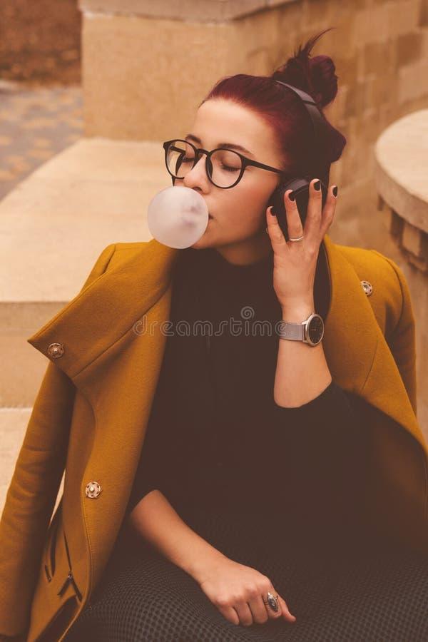 Chica joven linda que escucha la música en los auriculares en parque del otoño La muchacha tiene pelo de la berenjena La mujer so imagenes de archivo