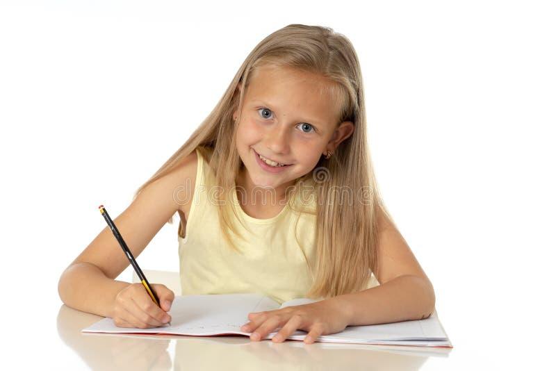 Chica joven linda que estudia en casa en un escritorio con un libro de estudio en un fondo blanco fotografía de archivo