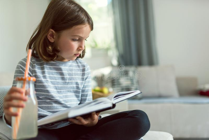 Chica joven linda que lee el libro emocionante y que bebe la limonada en casa fotografía de archivo