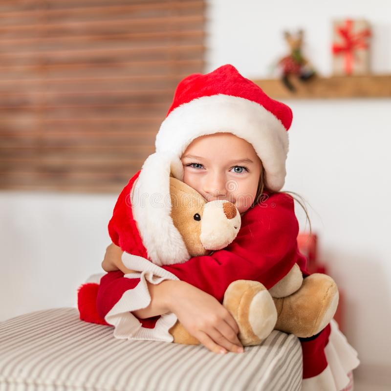 Chica joven linda que lleva el sombrero de santa que abraza su regalo de Navidad, oso de peluche suave del juguete Niño feliz con imagenes de archivo