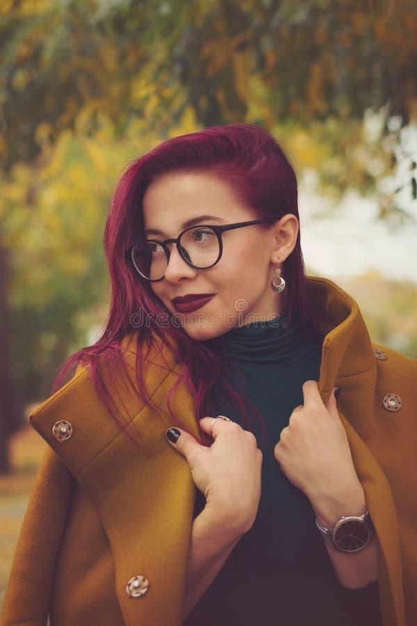 Chica joven linda que presenta en parque del otoño  Mujer que sonríe con el pelo imágenes de archivo libres de regalías