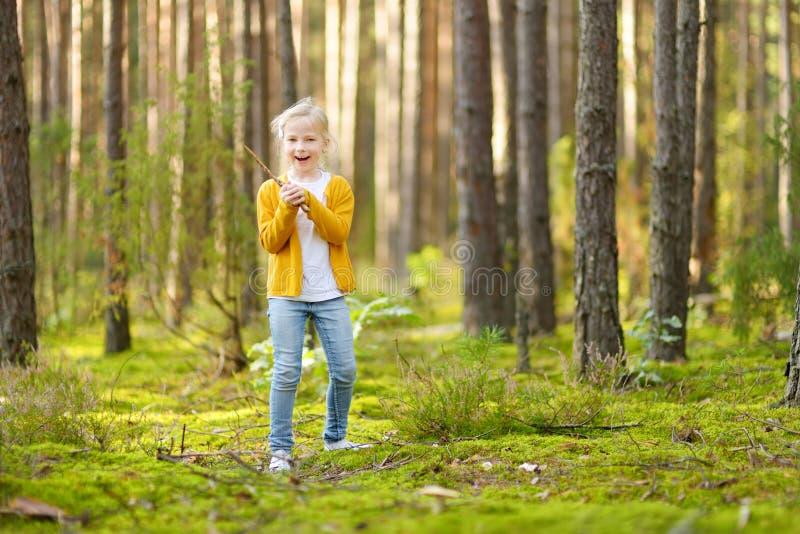 Chica joven linda que se divierte durante alza del bosque en d?a de verano hermoso Naturaleza de exploraci?n del ni?o fotos de archivo libres de regalías
