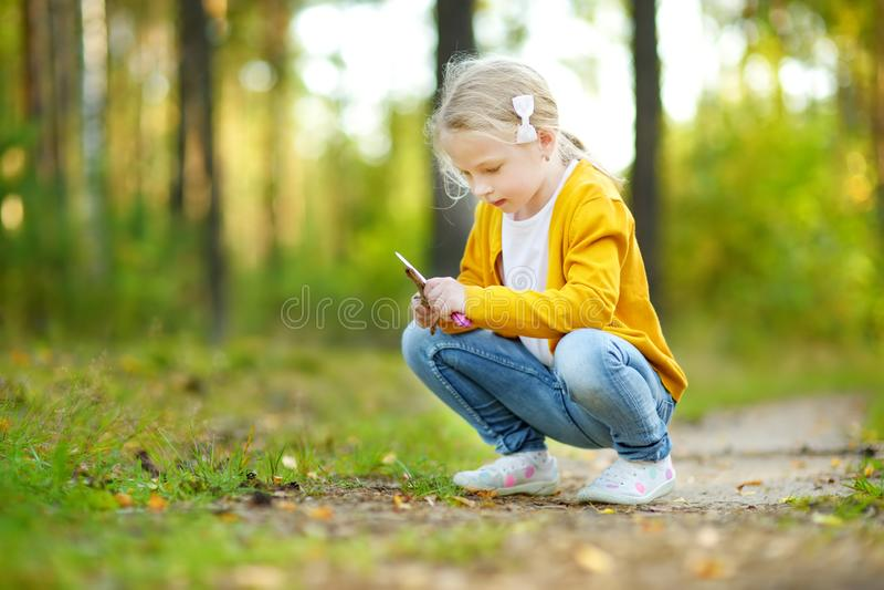 Chica joven linda que se divierte durante alza del bosque en d?a de verano hermoso Naturaleza de exploraci?n del ni?o imagen de archivo libre de regalías