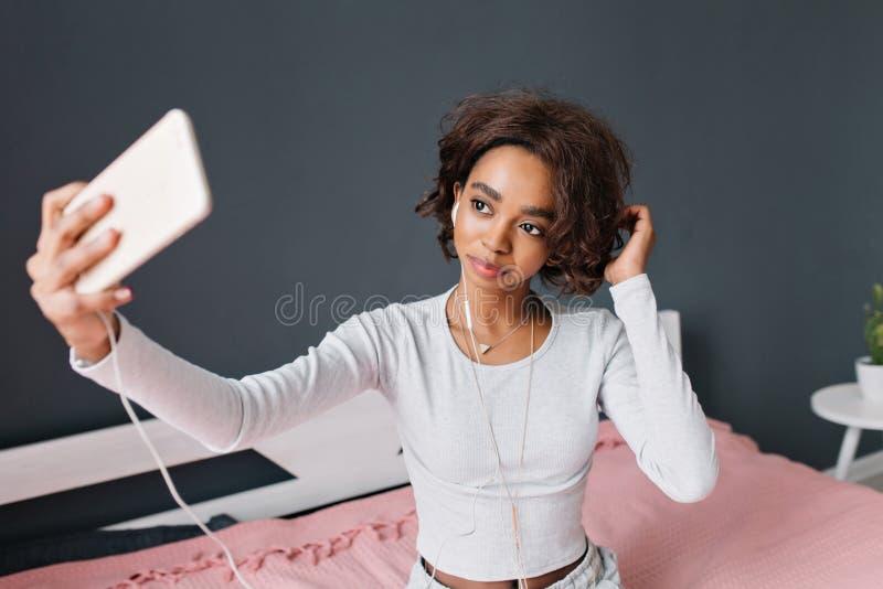Chica joven linda, selfie que toma adolescente, escuchando la música en cama con la alfombra rosada en sitio con la pared gris Lu imagen de archivo libre de regalías