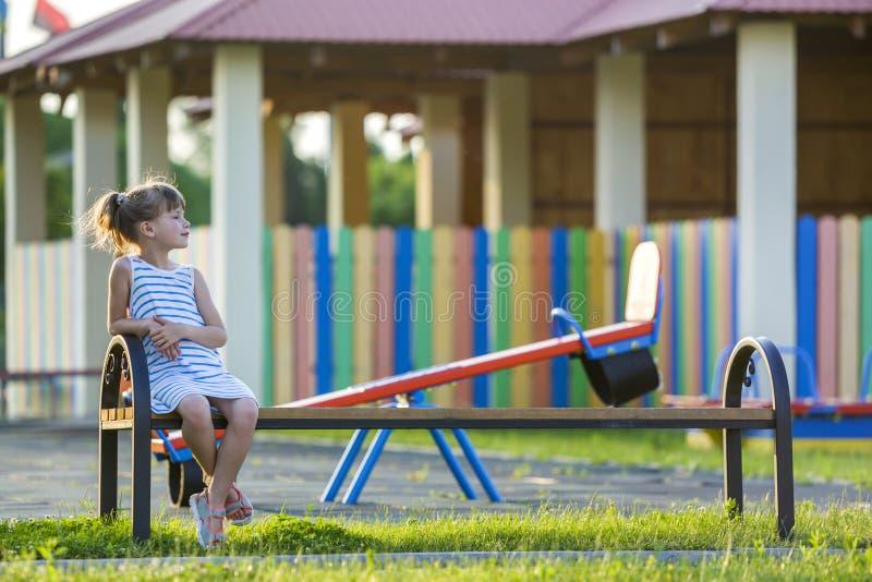 Chica joven linda sonriente que se sienta solamente al aire libre en banco en día de verano soleado foto de archivo libre de regalías