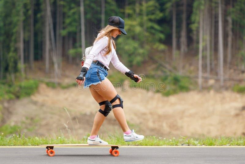 Chica joven longboarding cuesta abajo en el camino de la ladera foto de archivo libre de regalías
