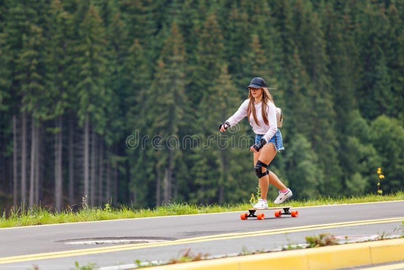Chica joven longboarding cuesta abajo en el camino de la ladera imagen de archivo libre de regalías