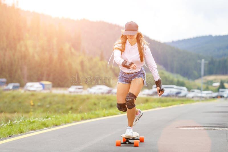 Chica joven longboarding cuesta abajo en el camino de la ladera fotografía de archivo