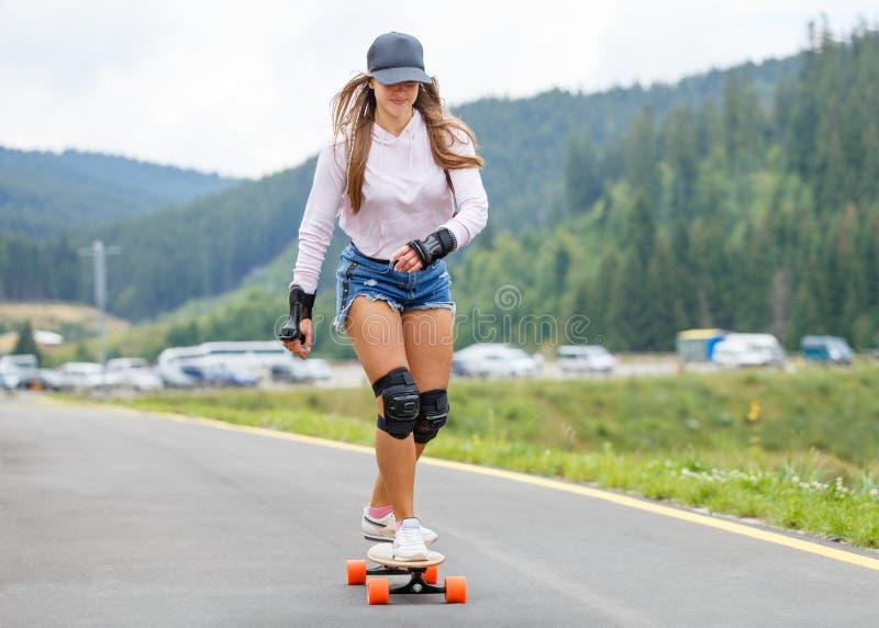 Chica joven longboarding cuesta abajo en el camino de la ladera fotos de archivo