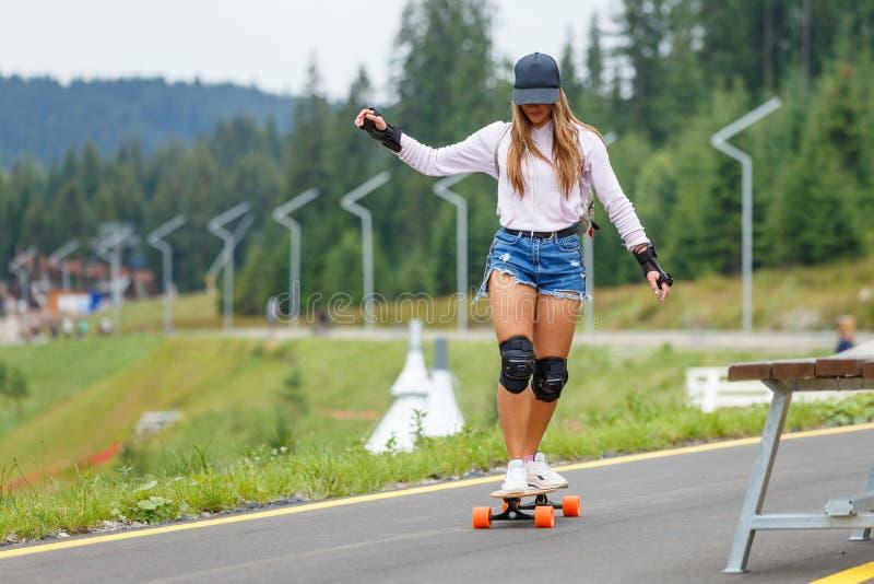 Chica joven longboarding cuesta abajo en el camino de la ladera imagenes de archivo