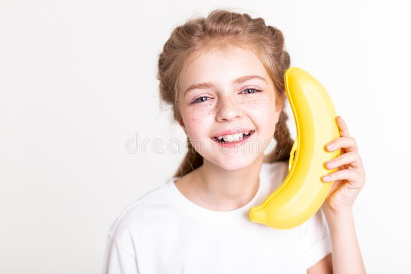 Chica joven luz-cabelluda de risa que sostiene el plátano plástico cerca de su oído foto de archivo