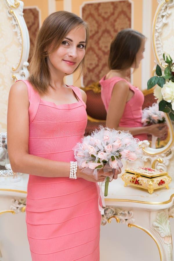Chica joven magnífica que coloca y que sostiene las flores fotografía de archivo libre de regalías