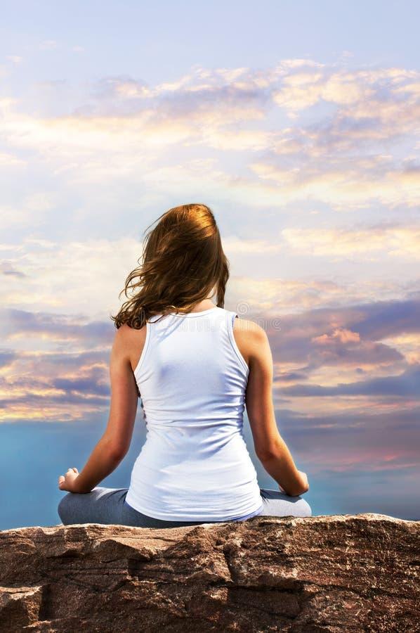 Chica joven meditating en la puesta del sol imagenes de archivo