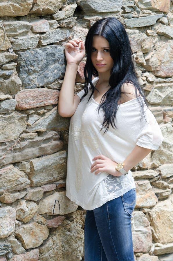 Chica joven morena en la camisa y la mezclilla blancas fotos de archivo