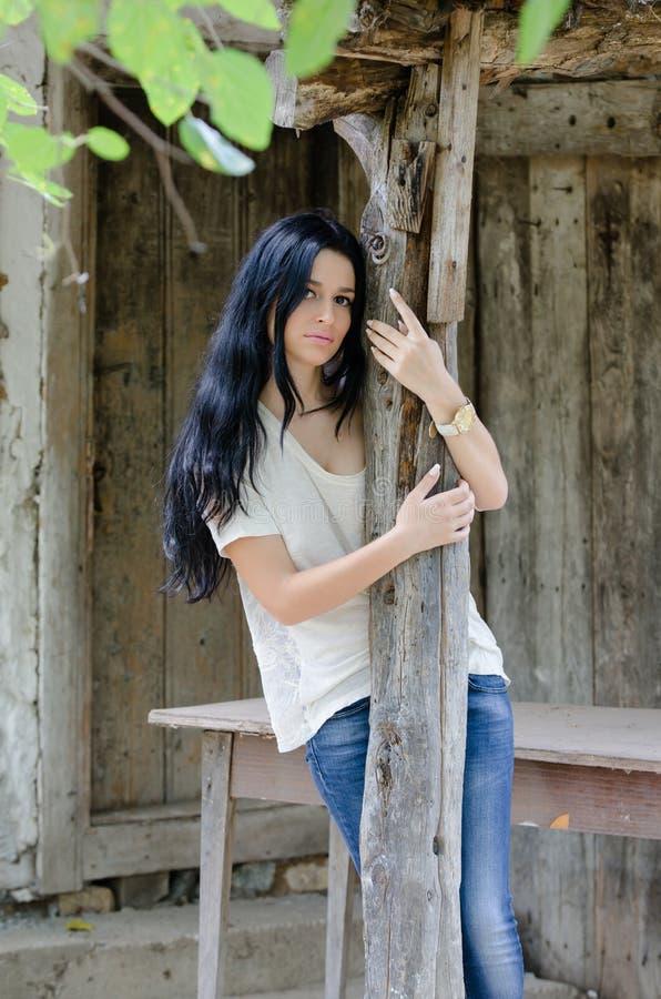 Chica joven morena en la camisa y la mezclilla blancas imagen de archivo