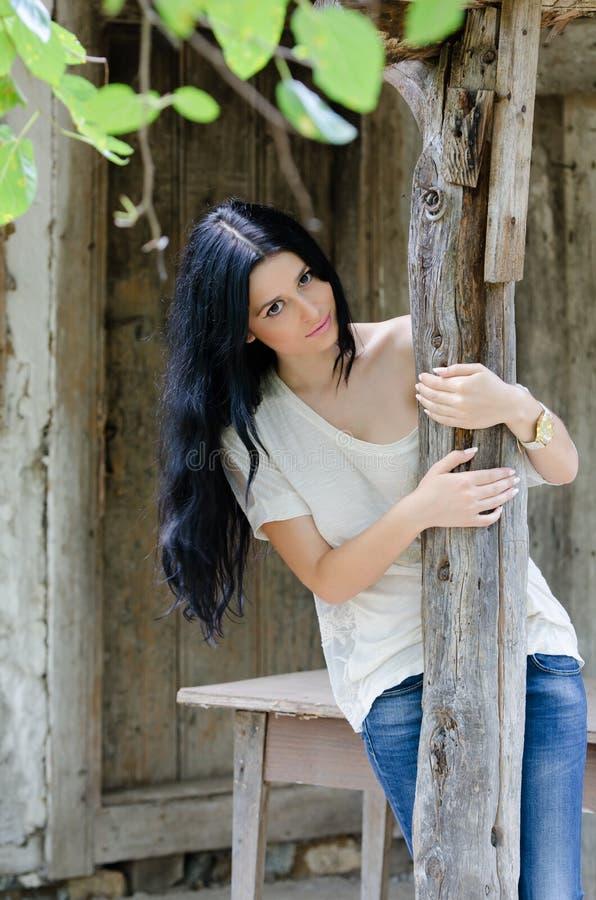 Chica joven morena en la camisa y la mezclilla blancas fotografía de archivo