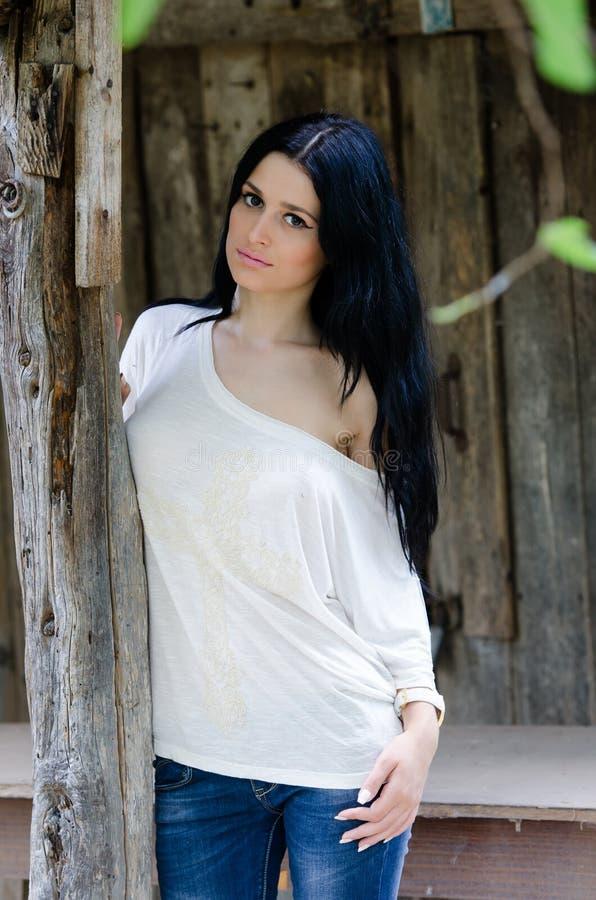 Chica joven morena en la camisa y la mezclilla blancas imagen de archivo libre de regalías