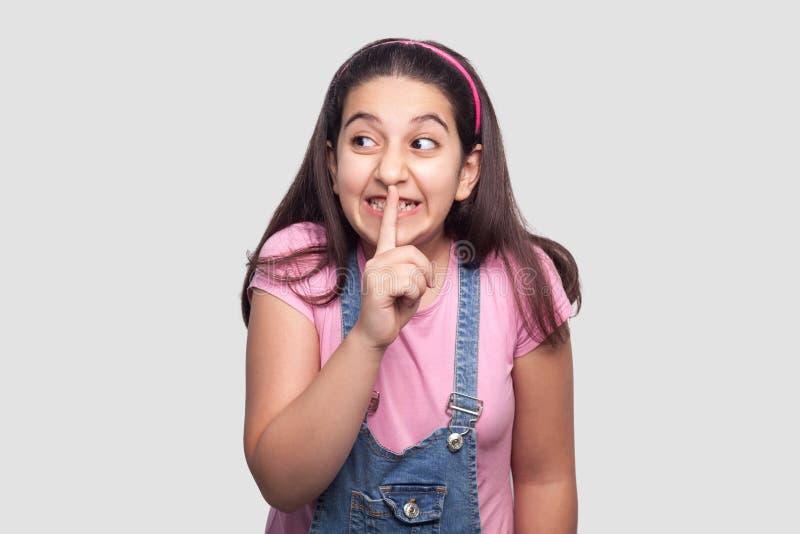 Chica joven morena hermosa divertida en la camiseta rosada casual, situación azul de los guardapolvos, diciendo sonrisa secreta,  imagen de archivo libre de regalías