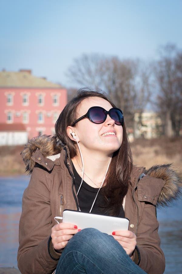 Chica joven/mujer bonitas con música que escucha de las lentes de sol negros imágenes de archivo libres de regalías