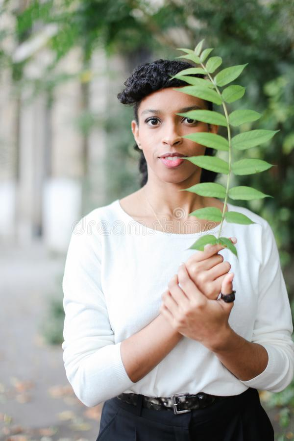 Chica joven negra que se coloca con la hoja verde, teniendo blusa blanca de las explosiones y el llevar foto de archivo