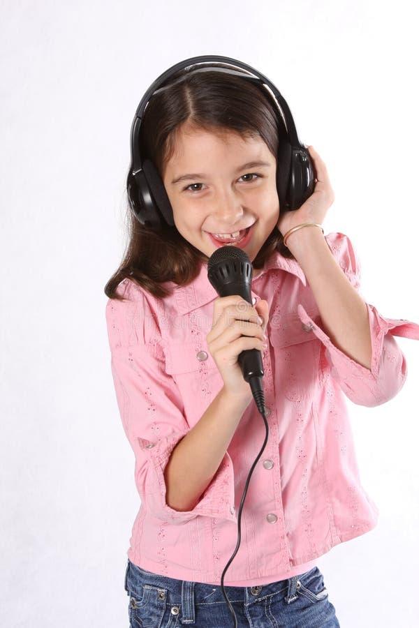 Chica joven/niño que canta con el micrófono foto de archivo
