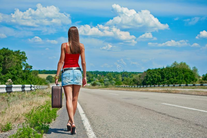 Chica joven o mujer hermosa en mini con la maleta que hace autostop a lo largo de un camino fotos de archivo