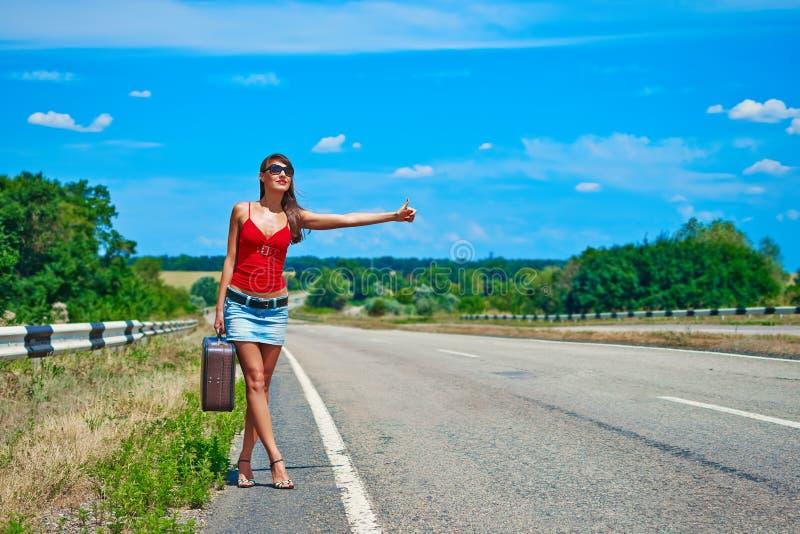 Chica joven o mujer hermosa en mini con la maleta que hace autostop a lo largo de un camino fotos de archivo libres de regalías
