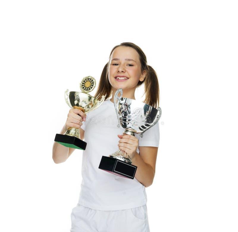 Chica joven orgullosa que sostiene dos trofeos fotos de archivo libres de regalías