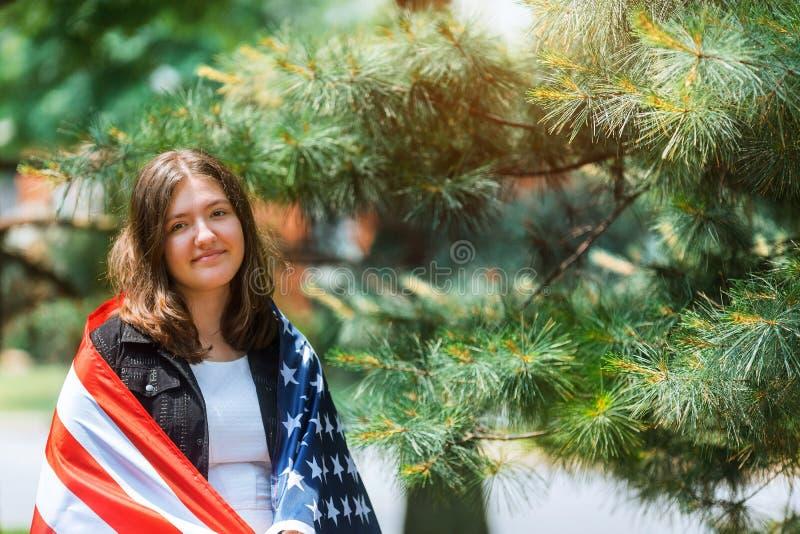 Chica joven patri?tica hermosa con la bandera americana sostenida en sus manos extendidas que colocan D?a de la Independencia fotografía de archivo